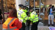 La policía arresta a un hombre disfrazado de brocoli en las protestas contra el cambio climático en Londres